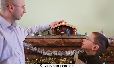 Father stands with son in front of fireplace on Christmas