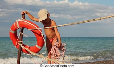 Girl puts a rope and poses next to lifebuoy ring against the...