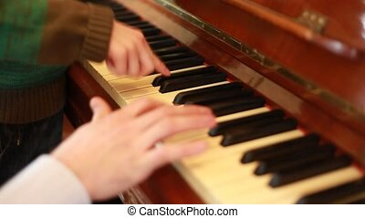 Closeup of hands of father and son playing on piano -...