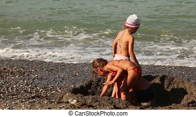 Three children dig a pit in the sand before the sea water -...