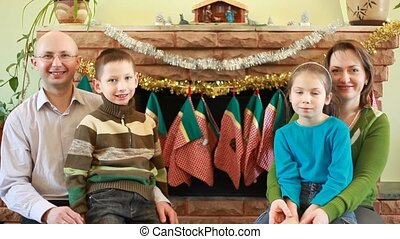 Family of four sitting in front of fireplace
