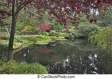 Cloudy day. - Lake and trees in well-known gardens Butchart...