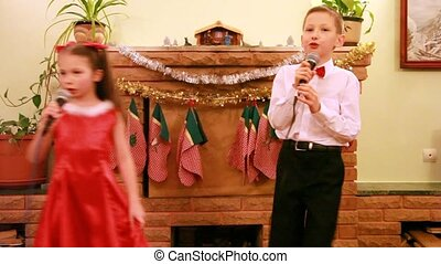 Sister and brother dance and sing song into microphone -...