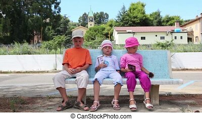 Three children sitting on the bench - Three children, a boy...