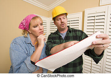Contractor in Hard Hat Discussing Plans with Woman - Male...