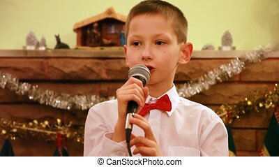 Boy sings Christmas song into microphone - Boy in glasses...