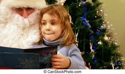Girl sitting in Santa Claus kneeling in front of the tree