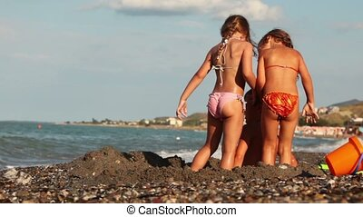 The boy and two girls playing in a sand pit on the...