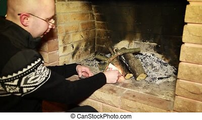 Man kindle fire in fireplace - man in cardigan and...