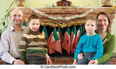 Brother and sister sit parents in front of fireplace