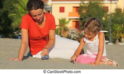 Mother and her daughter sitting on sand and writing on it by...