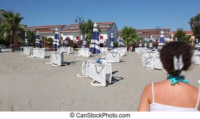 Woman runing away by sand between lot of deckchairs - Young...