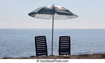 Two empty deckchairs stand on beach under parasol at sunny...