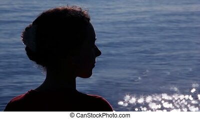 Silhouette of woman turned head with sun patterns on water...