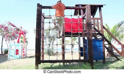 Two kids on playground, climbing on the obstacle - Two kids,...