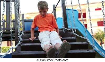 A boy sits on the stairs, hanging by chains, and swings from...