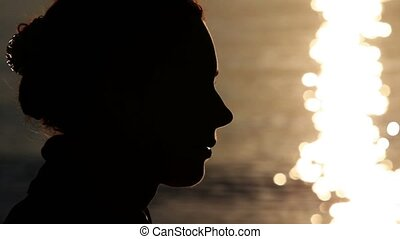 Silhouette of woman head with sunshine reflected in water...