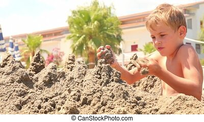 Boy sitting and build sand castle at sunny summer day