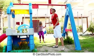 Mother helps daughter to sway at swing on playgroung -...