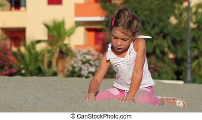 Little girl sitting on sand and writing on it by stick