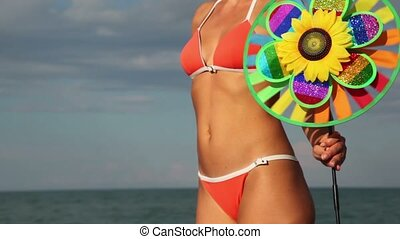 Woman's body with a colored toy, which rotates