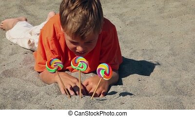 The boy lying on the sand, in front of him three candy, he...