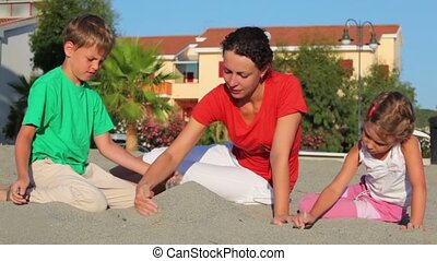 Mother and her kids sitting on sand, made sand pile