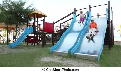 Two children are on playground object, boy sliding down -...