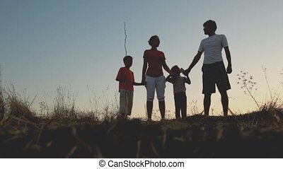 Parents and kids standing on hill