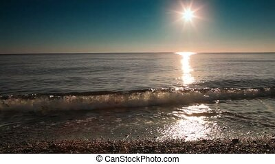 Surf washes part of the beach at sunset, sunshine reflect in...
