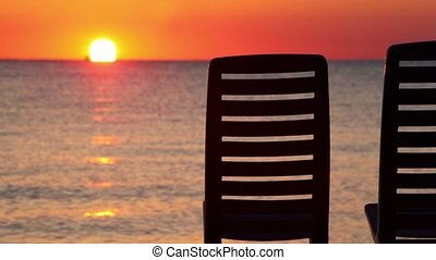 Seascape at evening sunset shown behind two deckchairs, ship...