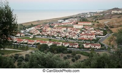 View from hill of costal village, sea and hills has shown -...
