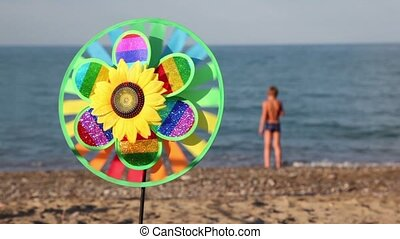 Toy in center, that spins on the background of sea and boy walking on shore