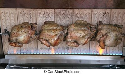 Four chicken are rosting in grill strunged on metallic...