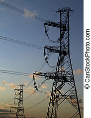 high voltage power pylons on against sunset sky