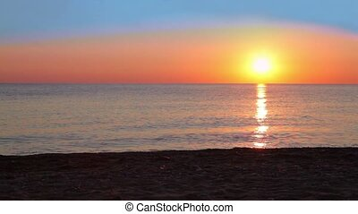 Seascape at sunset in summer evening, yellow red sky and sun...