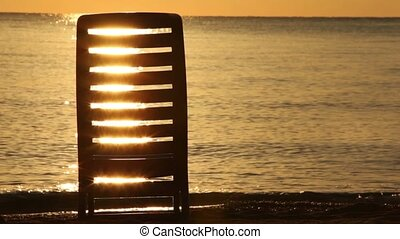 Deckchair stand in water and sunshine patterns shine through...