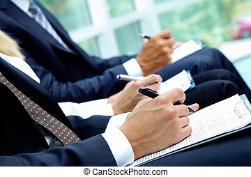 Writing lecture - Close-up of business people hands with...