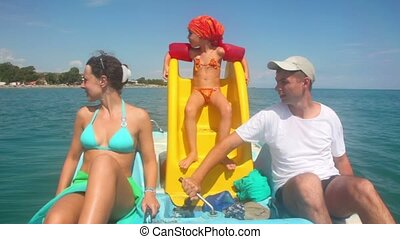 Father, mother and daughter sailing on catamaran