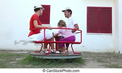 Parents and their daughter, rotating on a carousel, father...