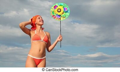 Woman holding toy that spins on the background of sky -...