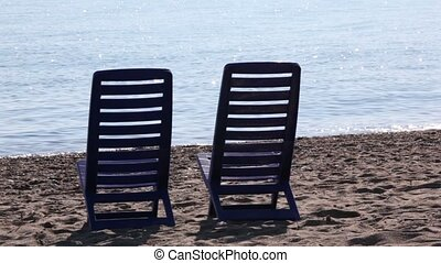 Two empty deckchairs stand on beach
