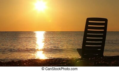 Deckchair stand in sea, sunset