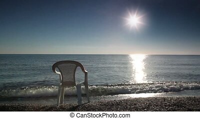One chair stands in water washed by sea surf, sunshine...