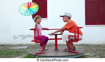 Two children spinning on the carousel