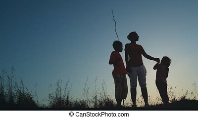 Mother and kids standing on hill, boy holding long thin...
