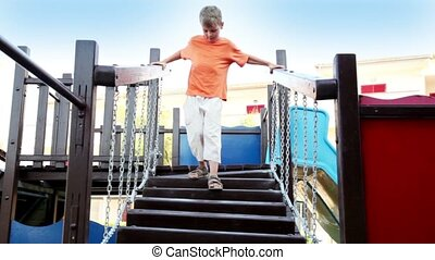 The boy on playground goes down the stairs, hanging on...