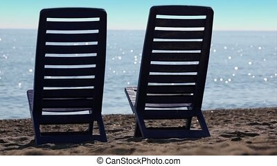 Two empty deckchairs stand on beach at sunny day, camera...