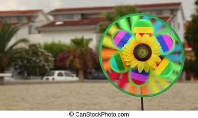 Round toy with sunflower in the center is set in the ground and spinning