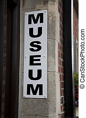 Museum Sign against Stone Wall ay Building Entrance